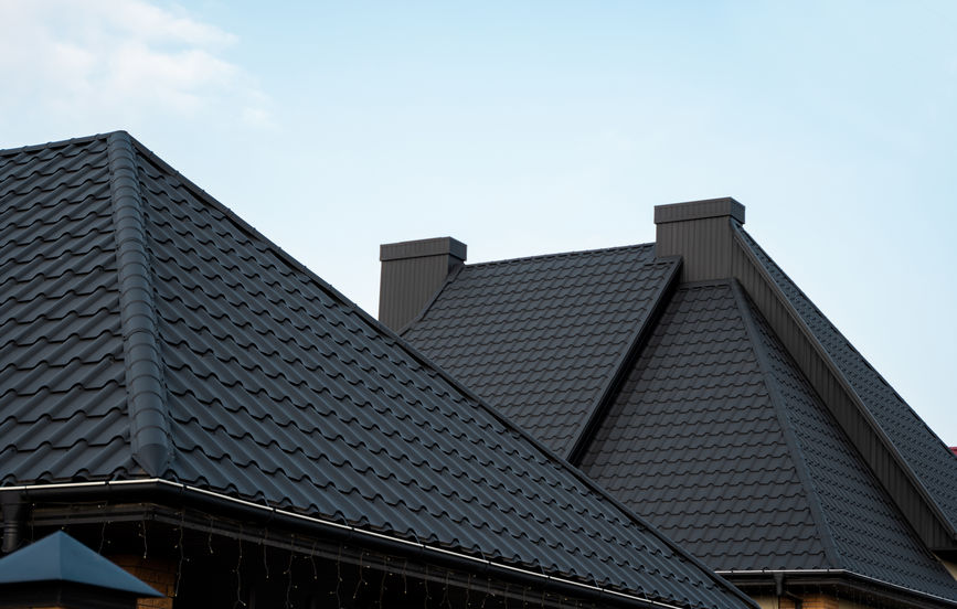 Black metal tile roof. Roof metal sheets. Modern types of roofing materials. Roof of the house, metal roof tile against the blue sky. Building