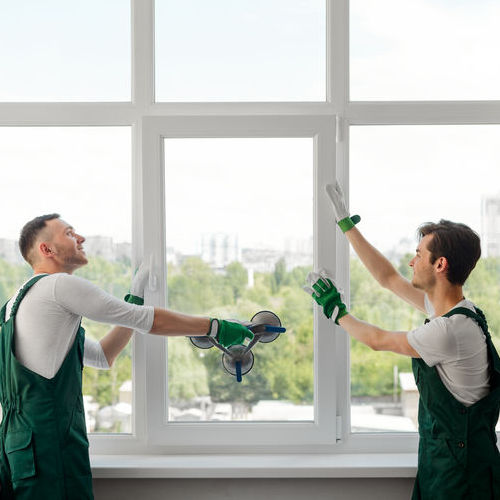 Two window installers. Positive mood and good job of young workers replacing a window in the living room.